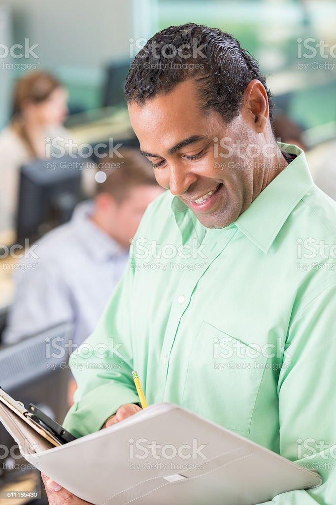 Confident teacher consults training manual before training class stock photo