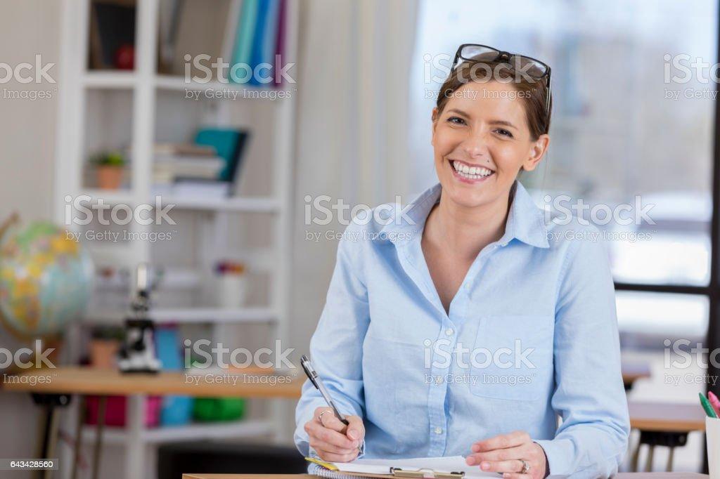 Confident teacher grades papers after school stock photo