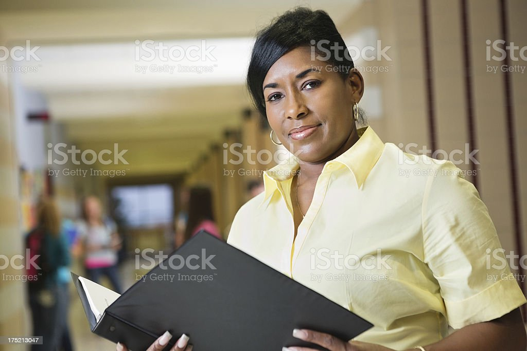 Confident teacher looking at lesson plan in high school hallway stock photo