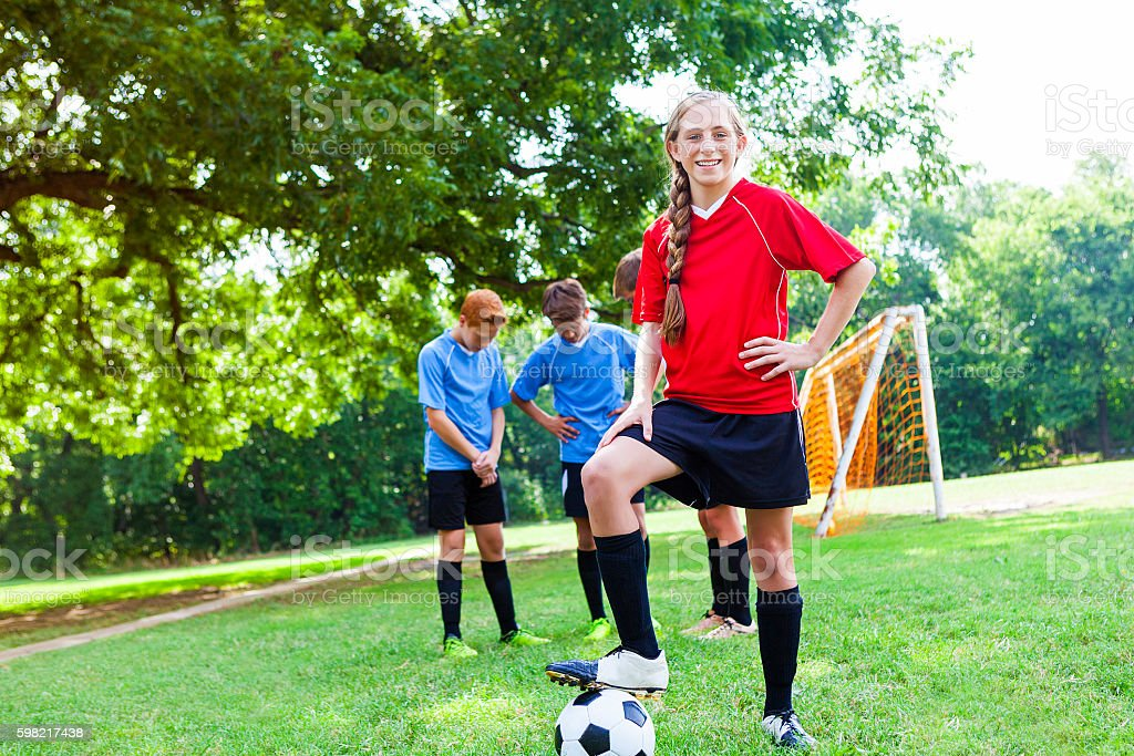 Confident teenage female soccer player poses with ball stock photo