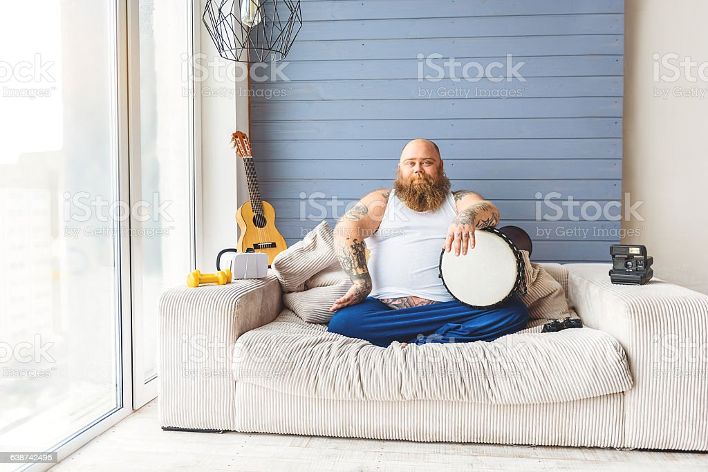 Confident thick guy playing musical instrument stock photo