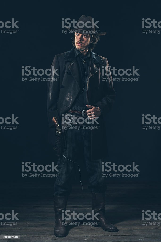 Confident vintage 1900 cowboy showing revolver. Ready to shoot. stock photo