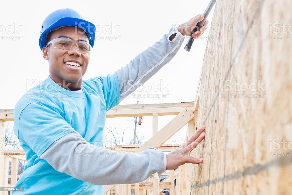 Confident volunteers uses hammer in charity home stock photo