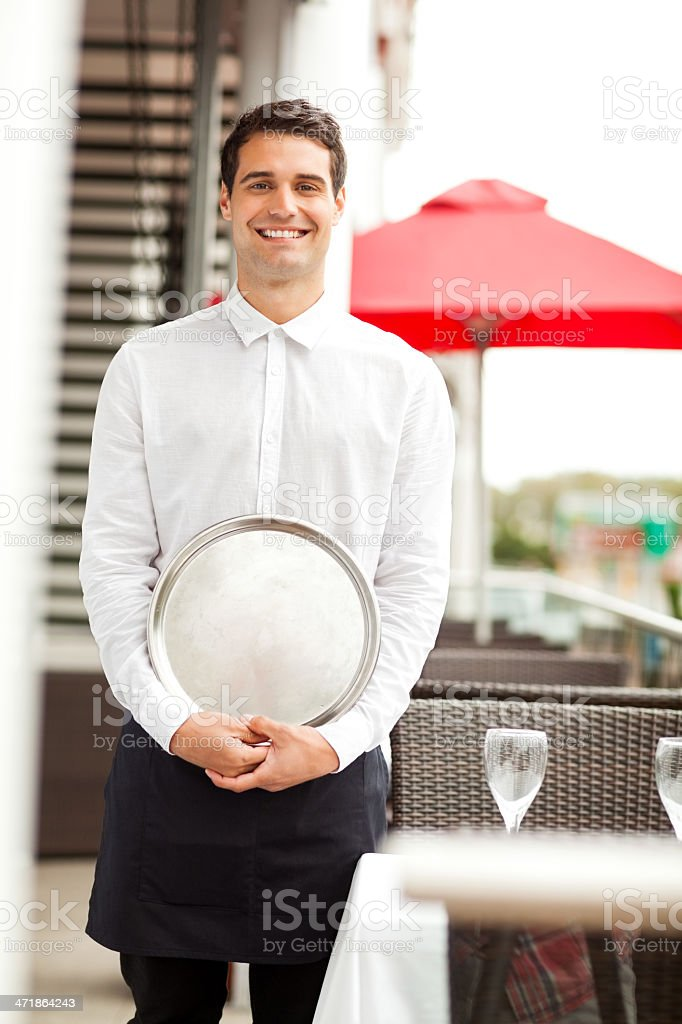 Confident Waiter With Serving Tray Smiling In Restaurant royalty-free stock photo