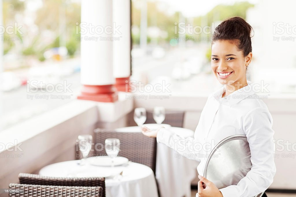 Confident Waitress Welcoming In Restaurant stock photo