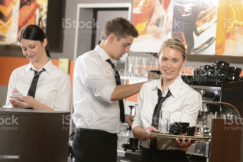 Confident waitresses and waiter working in bar royalty-free stock photo