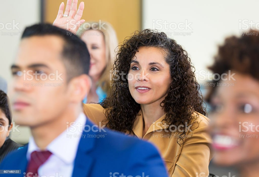 Confident woman asks question during meeting stock photo