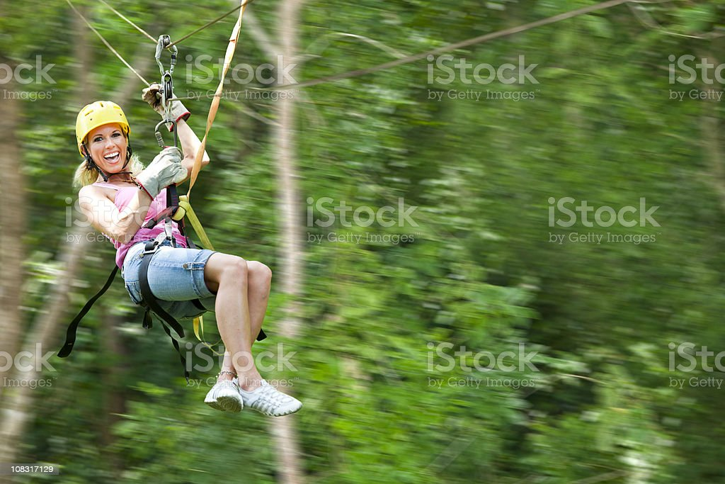 Confident woman flying through jungle stock photo