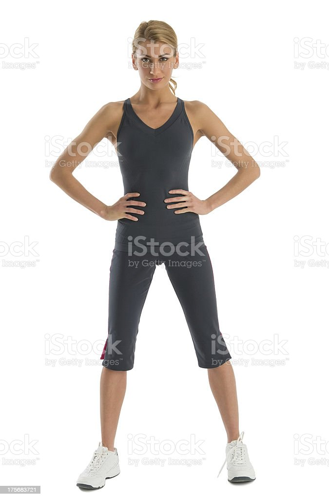 Confident Woman In Sports Clothing With Hands On Hips stock photo