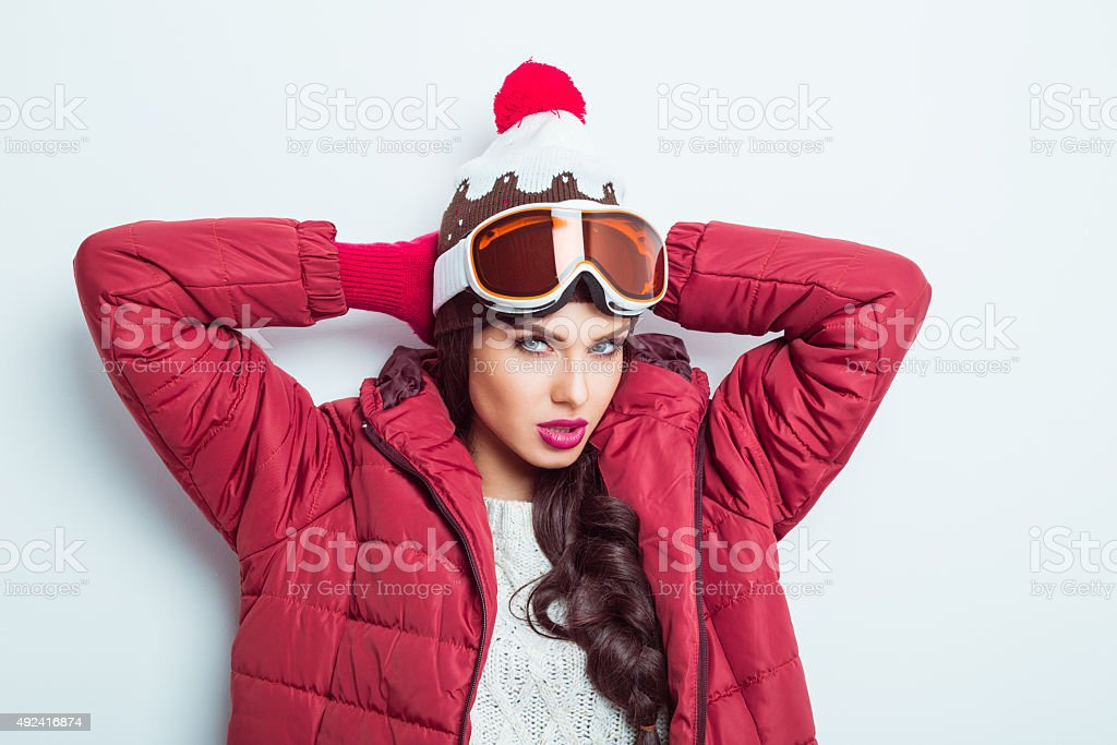 Confident woman in winter outfit, wearing cap and goggle stock photo