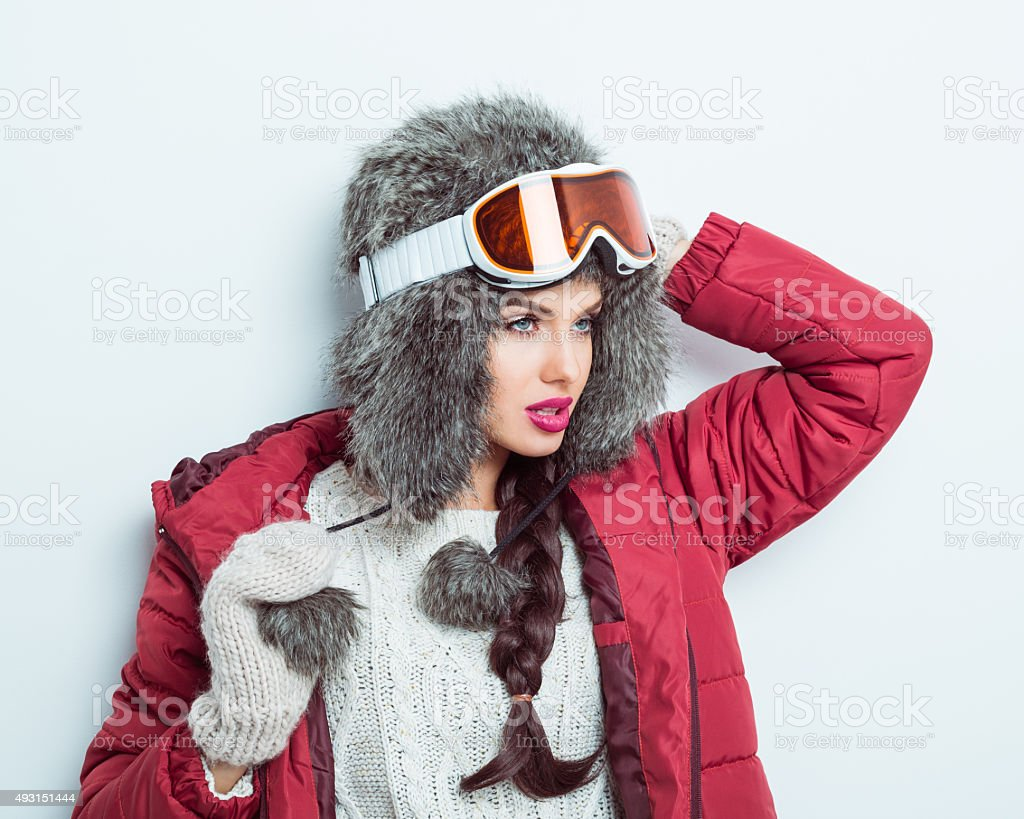Confident woman in winter outfit, wearing fur cap and goggle stock photo