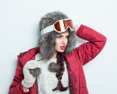 Confident woman in winter outfit, wearing fur cap and goggle