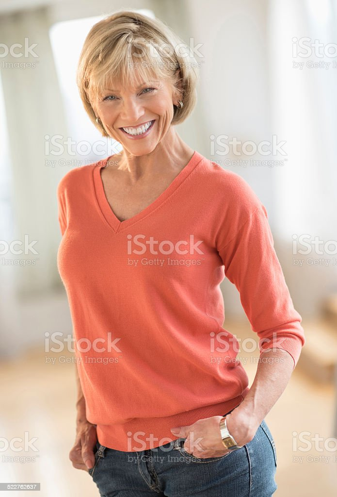 Confident Woman With Hands In Pockets Standing At Home stock photo