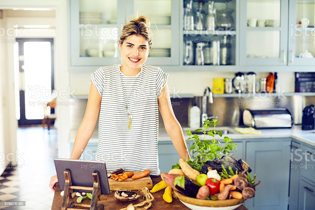Confident woman with vegetables and digital tablet in kitchen stock photo