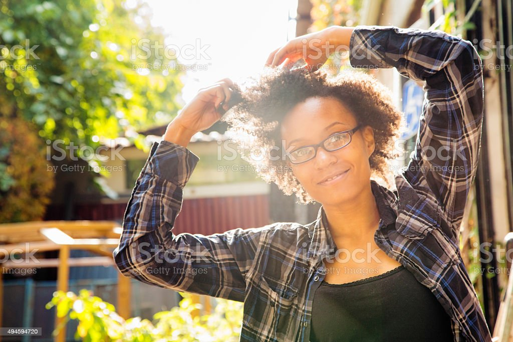 Confident young African American woman arranging her hair outdoors stock photo