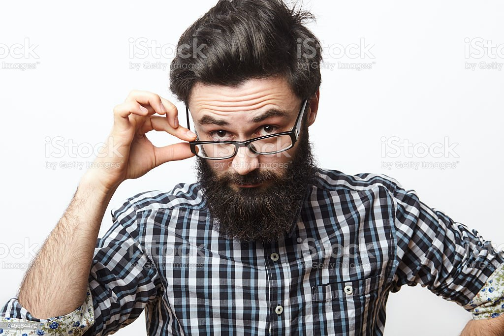Confident young bearded man in eyeglasses looking at camera stock photo