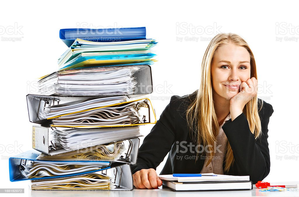 Confident young blonde businesswoman smiles despite huge workload royalty-free stock photo