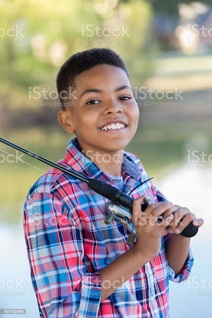 Confident young boy with fishing pole stock photo
