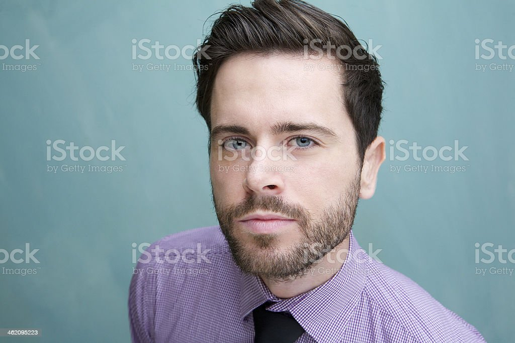 Confident young business man against blue background royalty-free stock photo