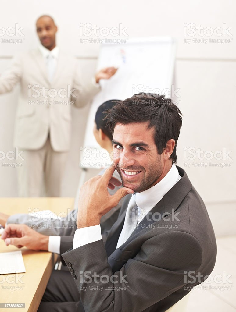 Confident young businessman at a presentation with colleagues royalty-free stock photo
