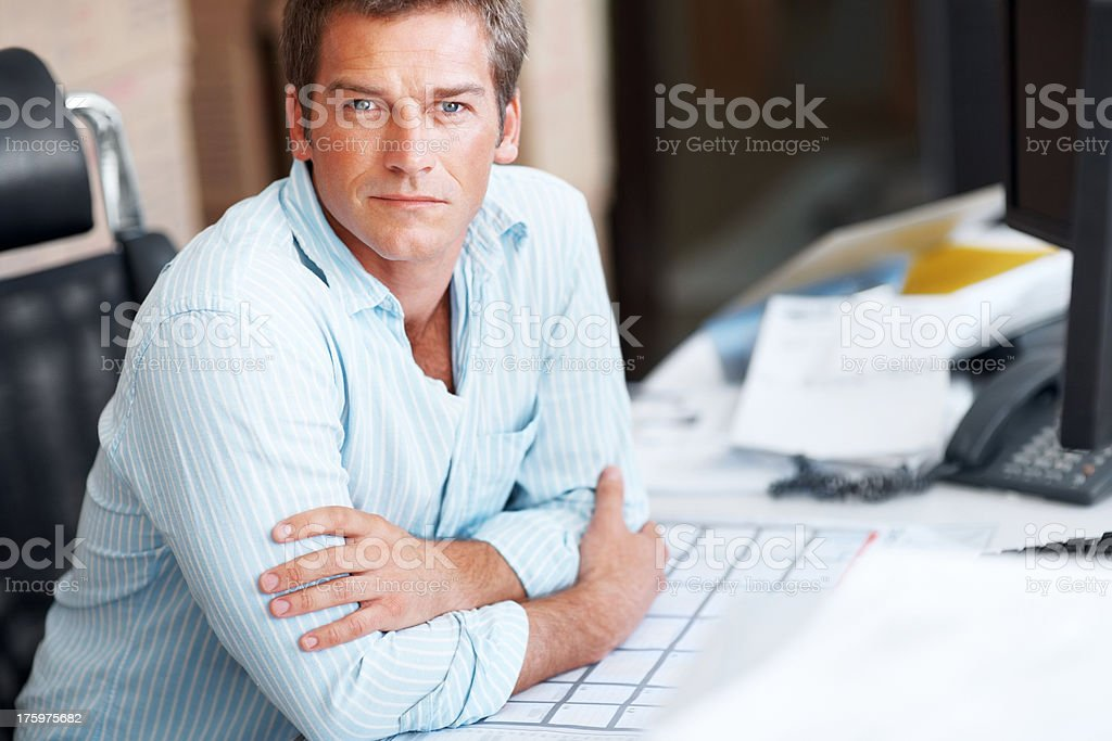 Confident young businessman sitting in office stock photo