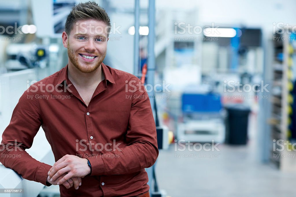 Confident young businessman standing in factory stock photo