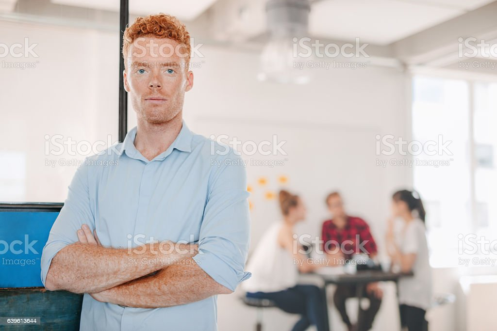 Confident young businessman standing in office stock photo