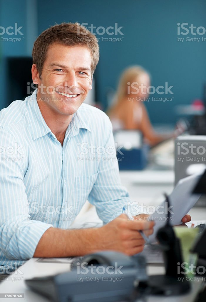 Confident young businessman working at office stock photo