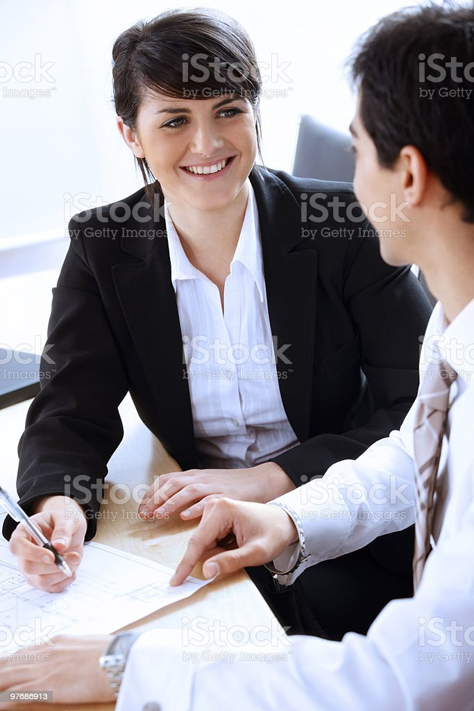 confident young businesswoman discussing reports with colleague in office stock photo