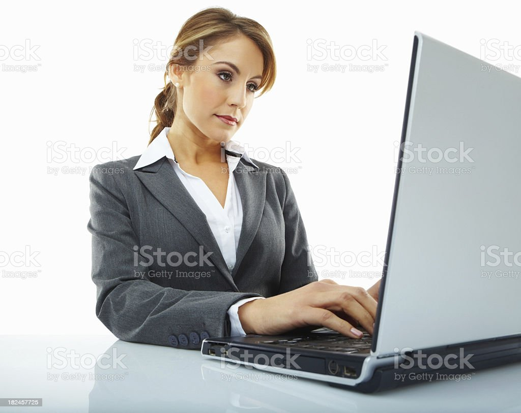 Confident young businesswoman working on a laptop royalty-free stock photo