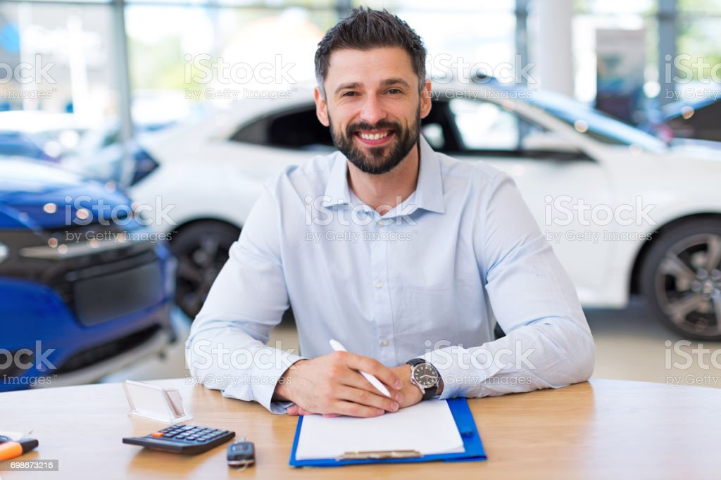 Confident young car dealer in showroom stock photo