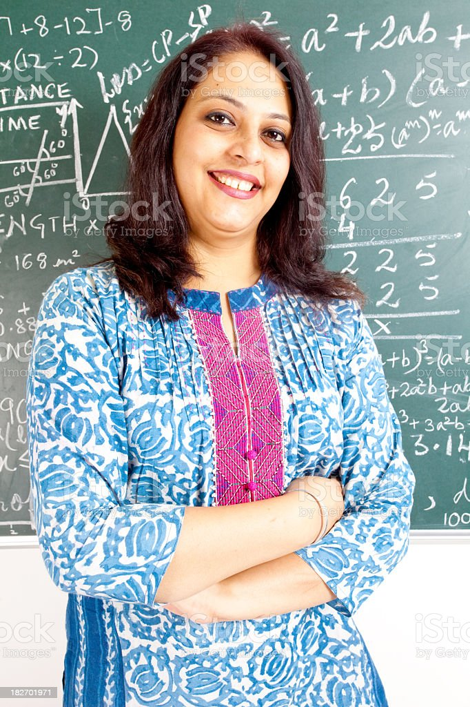 Confident Young Cheerful Indian Mathematics Teacher in a Classroom royalty-free stock photo