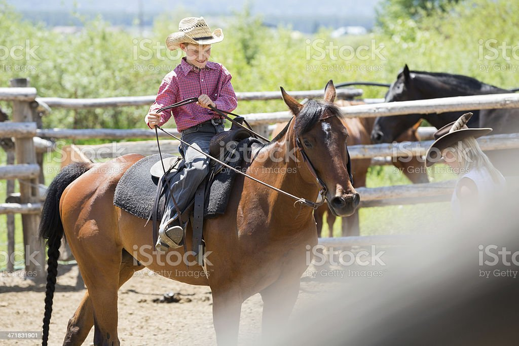 Confident young cowboy riding horse at family ranch royalty-free stock photo