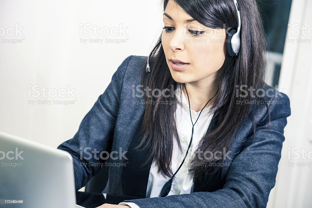 Confident young female customer service agent with headset royalty-free stock photo