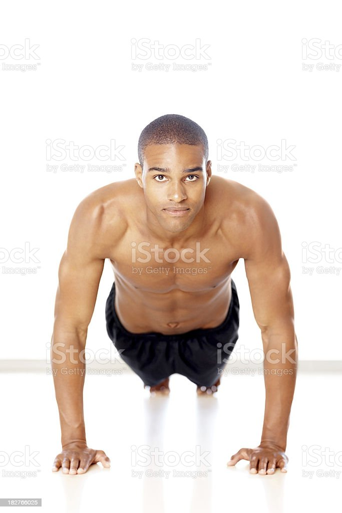 Confident young guy practicing push ups against white royalty-free stock photo