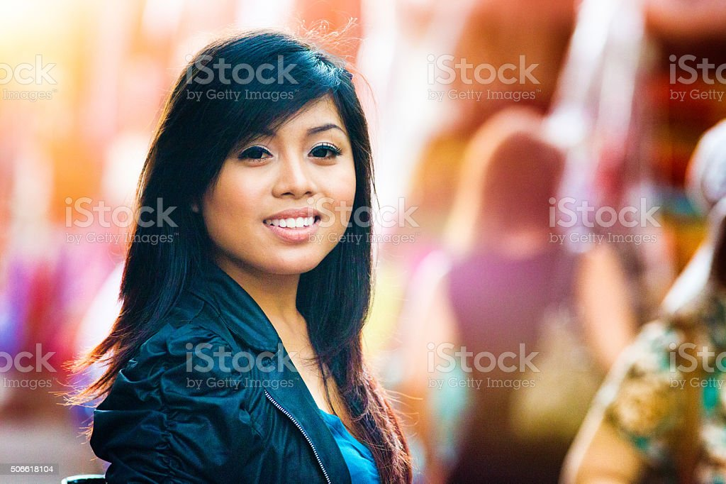 Confident young Indonesian woman smiling at Ubud's market stock photo
