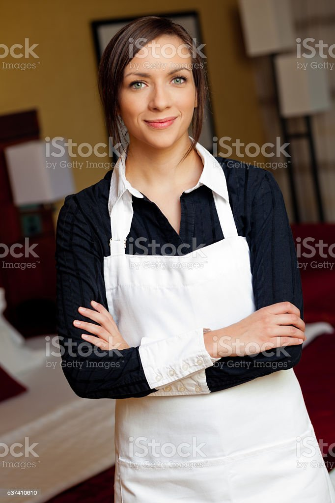 Confident young maid in luxury hotel room stock photo