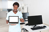 Confident Young Male Nurse Pointing At Laptop