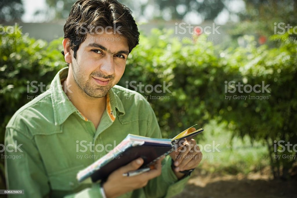 Confident young man in outdoor with diary looking at camera. stock photo