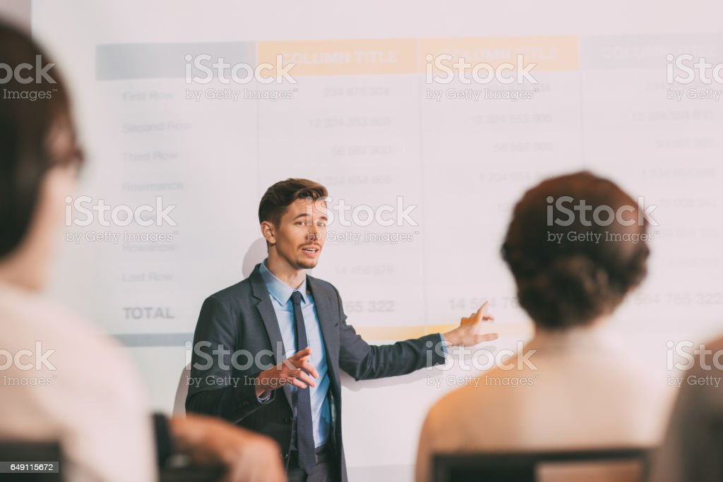 Confident Young Man Making Presentation to Team stock photo