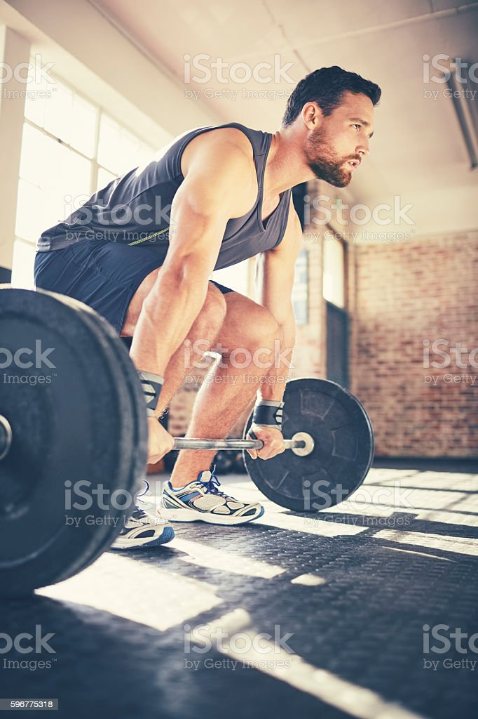 Confident young man picking up barbell in gym stock photo
