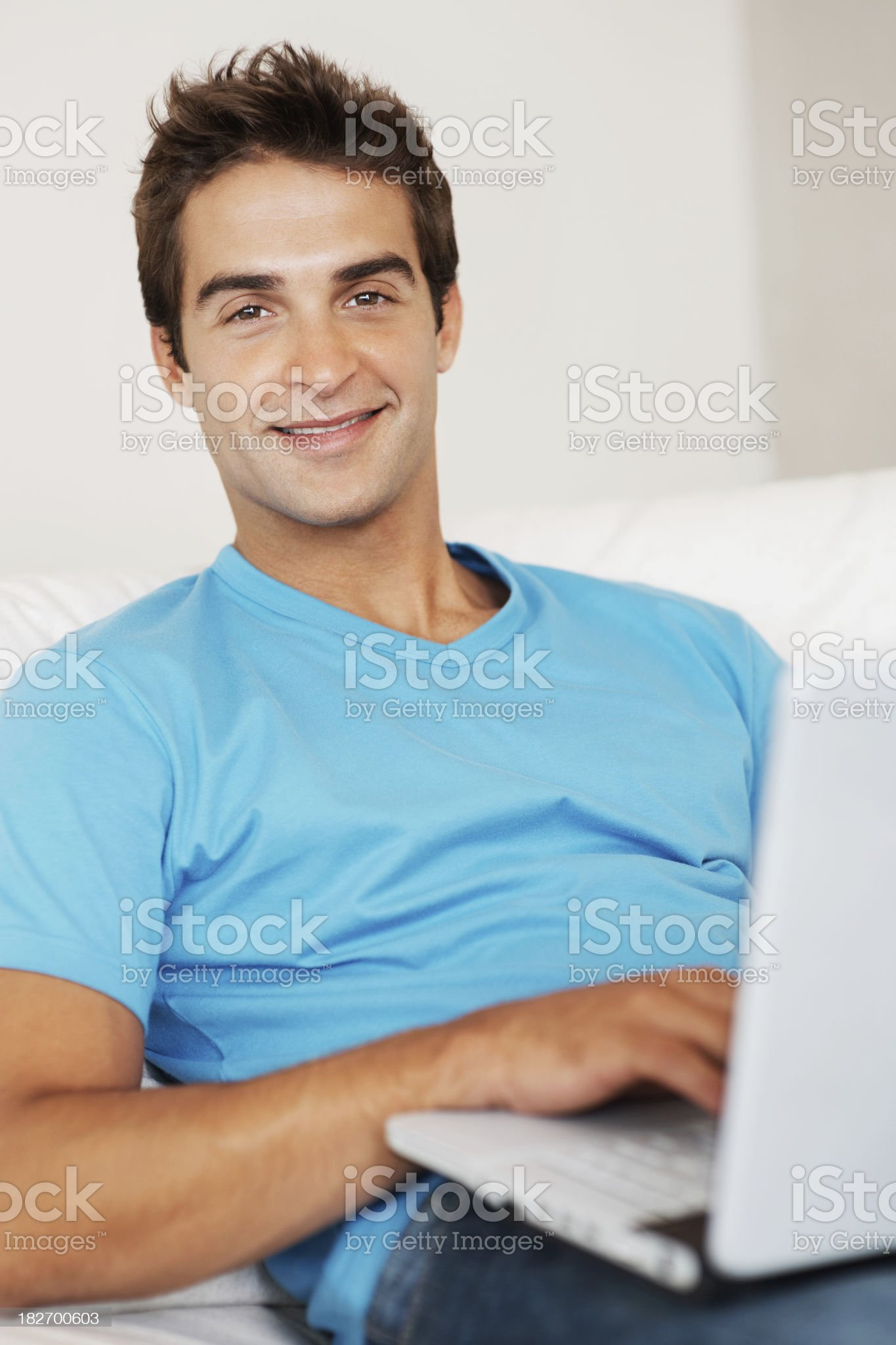 Confident young man using a laptop in bedroom royalty-free stock photo