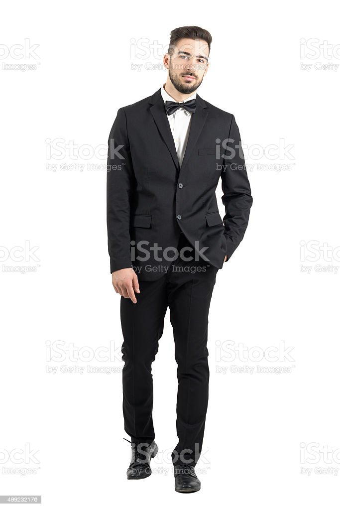 Confident young man with hands in pocket walking towards camera stock photo