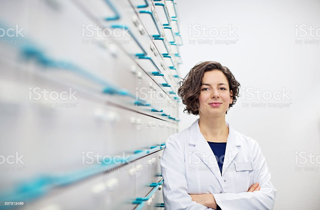 Confident young pharmacist standing by a medicine shelf stock photo