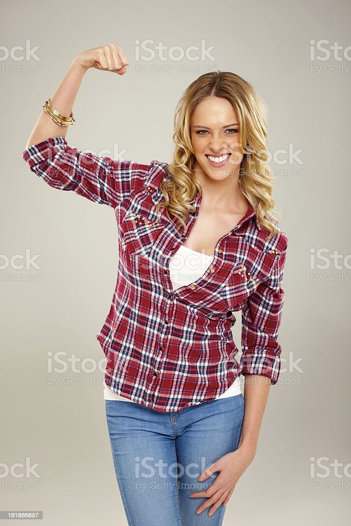 Confident young woman flexing her biceps against grey stock photo