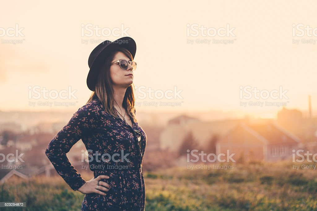 Confident young woman in retro style clothing spectating nature stock photo