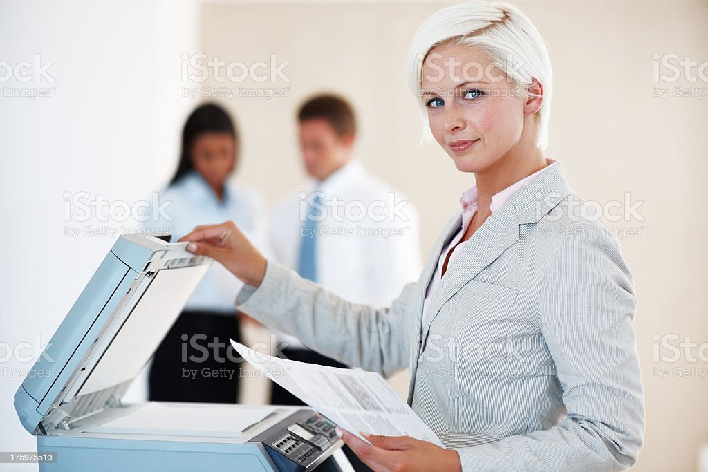 Confident young woman photocopying at the office stock photo