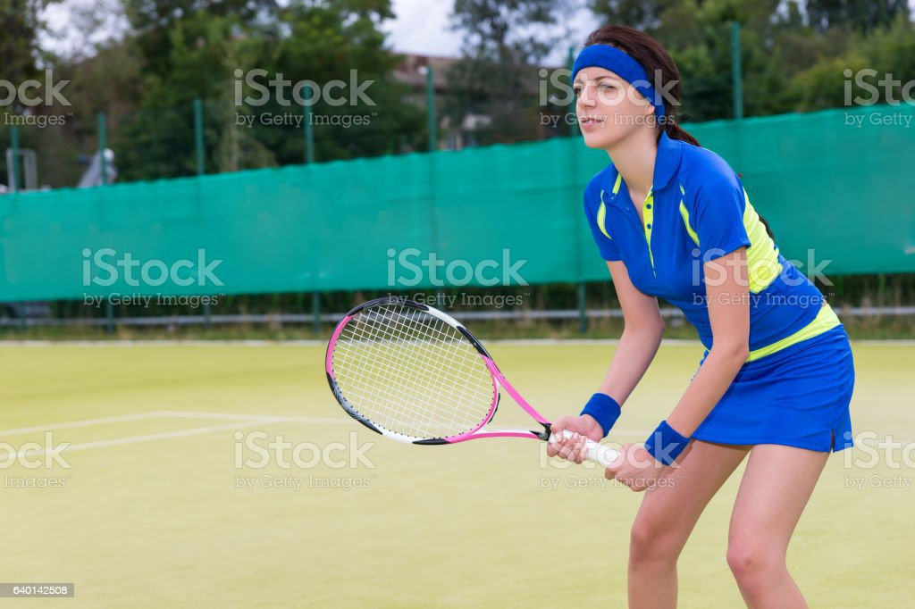 Confident young woman playing tennis on tennis court stock photo