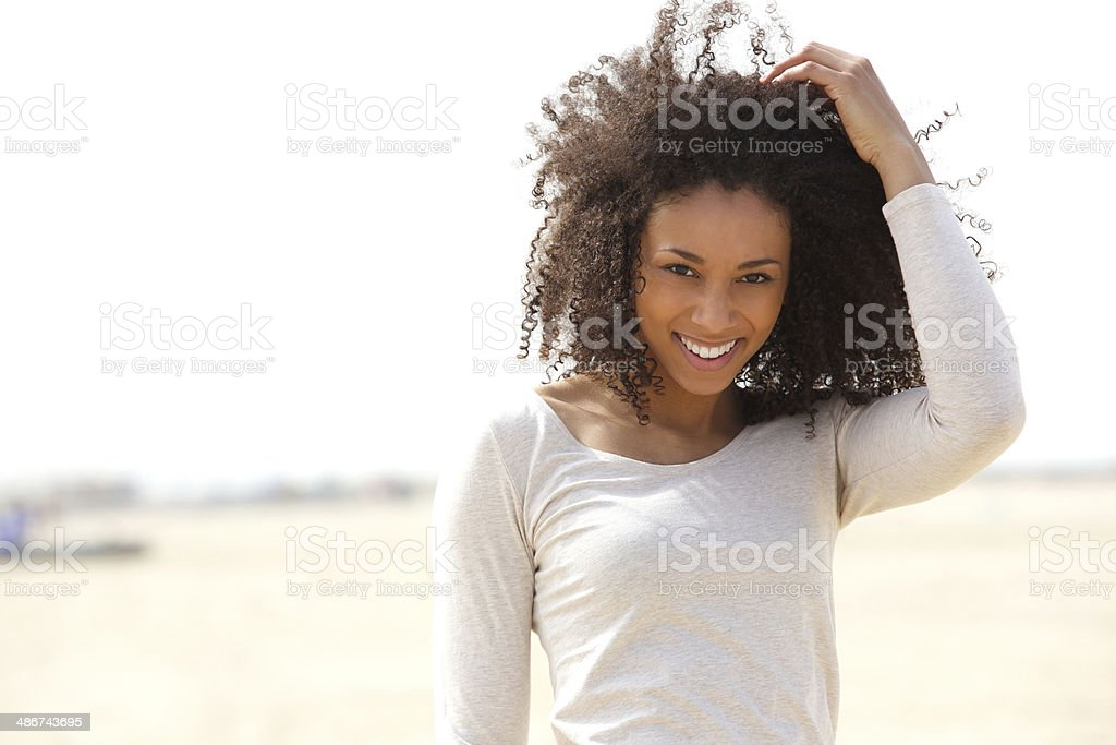 Confident young woman smiling outdoors stock photo