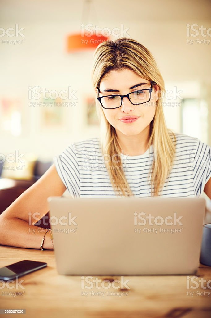 Confident young woman using laptop at home stock photo